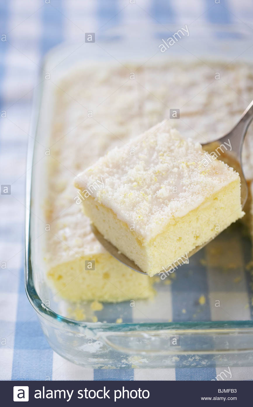 Lifting A Piece Of Lemon Buttermilk Sheet Cake From Pan Stock Photo