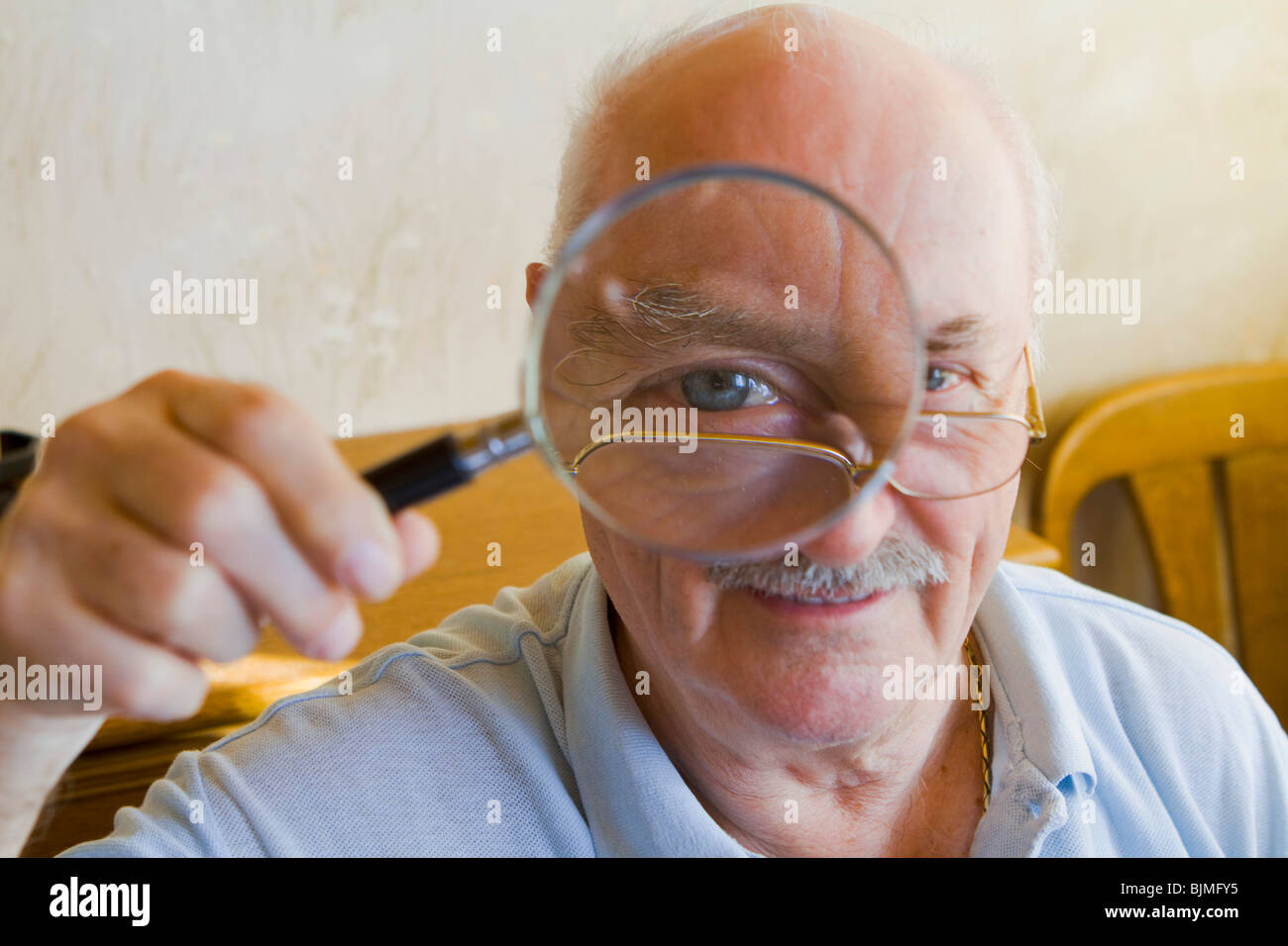 Pensioner looking through a magnifying glass - Stock Image
