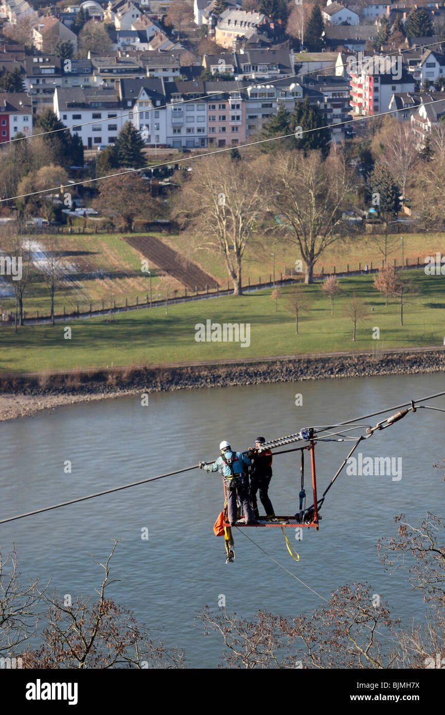 Workers in a safety cage navigate the suspension cable of a cable car which will connect the Deutsches Eck headland - Stock Image