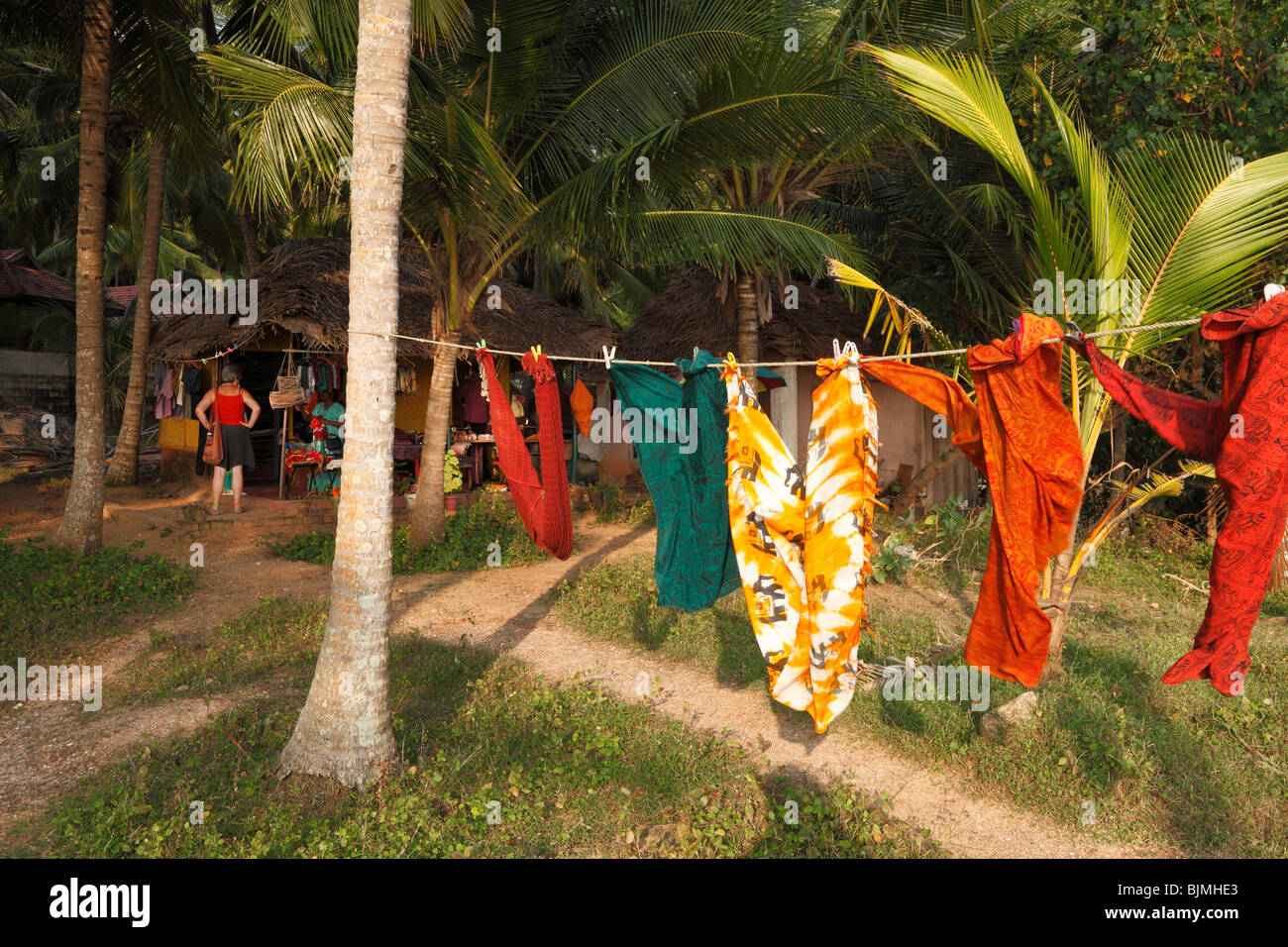 Fabrics hanging on a clothesline, sewing hut under palms, south of Kovalam, Kerala state, India, Asia - Stock Image