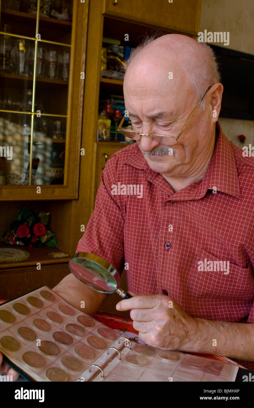 Pensioner looking at his coin collection with a magnifying glass - Stock Image