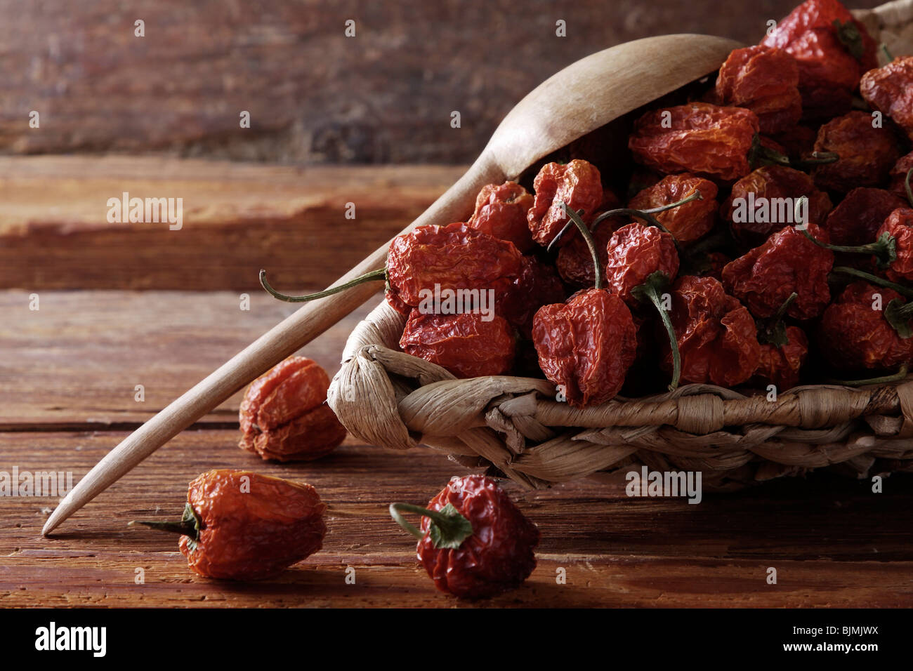 Mini-Peppers (capsicum) in a wicker basket on a rustic wooden background Stock Photo