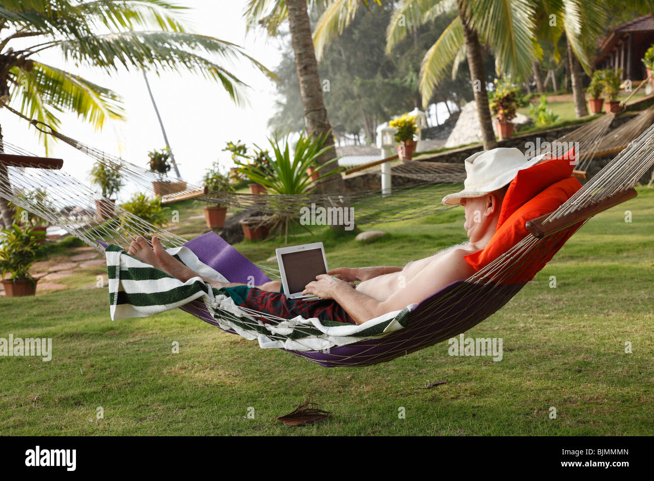 Man wearing a hat, lying in a hammock under palm trees and relaxing while working with a netbook, Bethsaida Hermitage - Stock Image