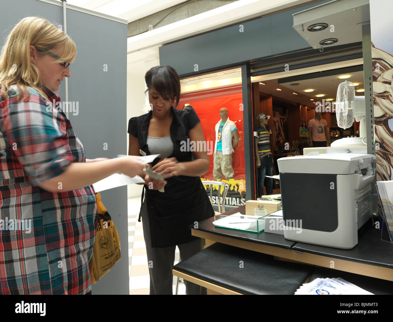 Woman Getting Her Jewellery Valued At Gold Bar in a Shopping Mall Gold Jewellery Sold for Cash - Stock Image