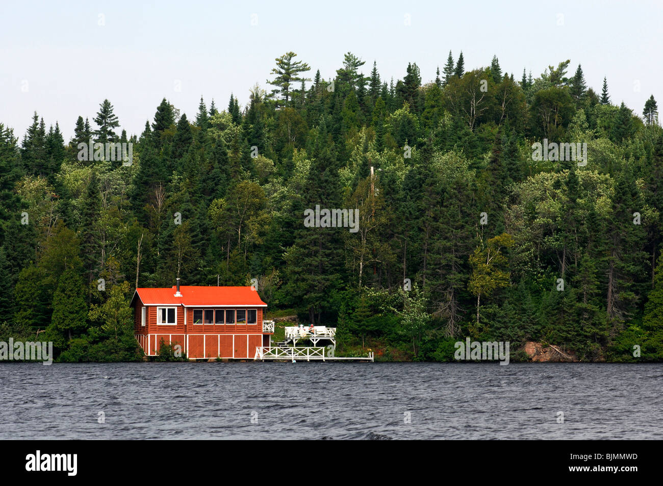 Lonely house with red roof standing at a forest lake in front of a wooded hill, Quebec, Canada - Stock Image