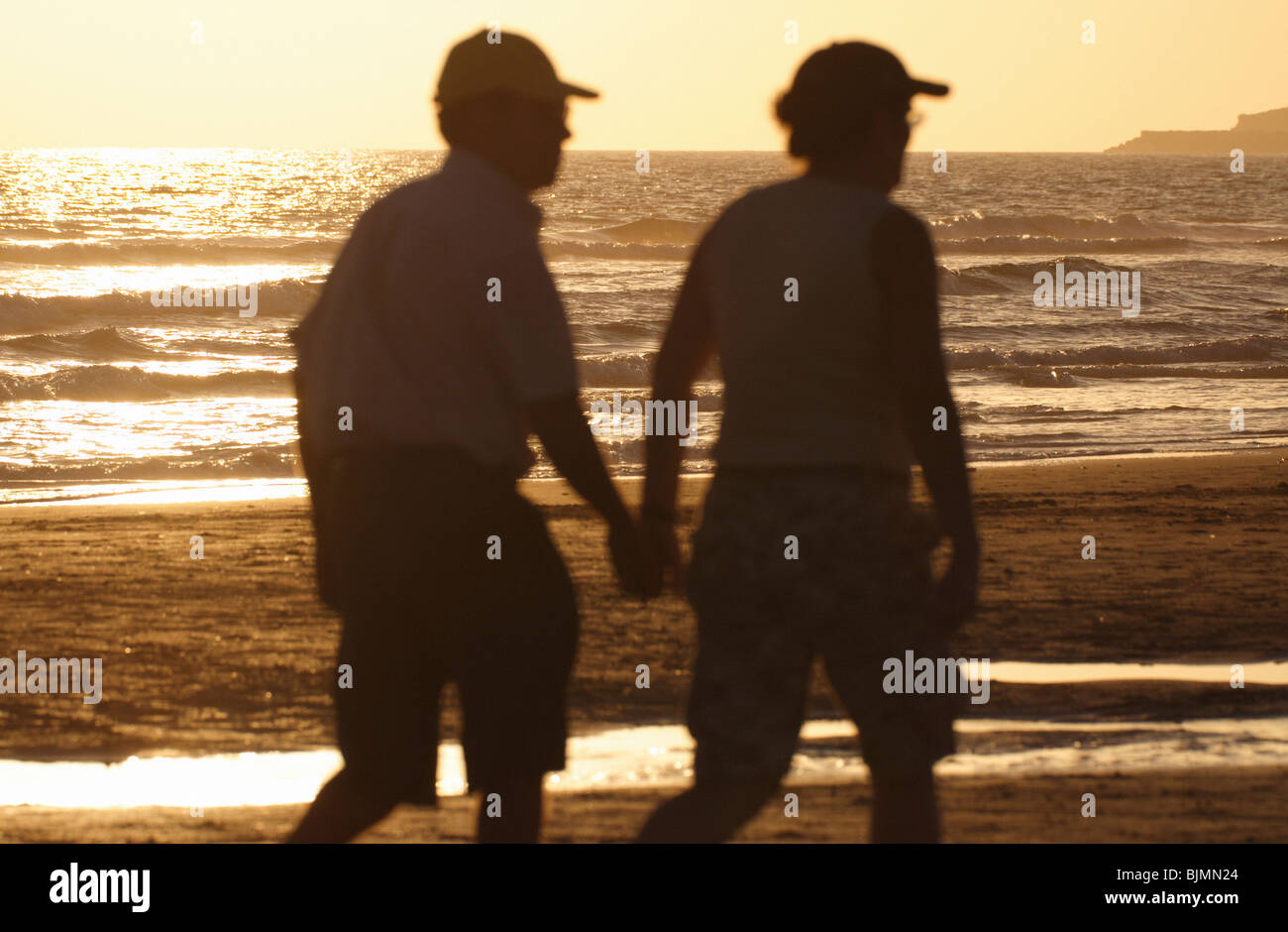 Elderly couple walking on a beach - Stock Image