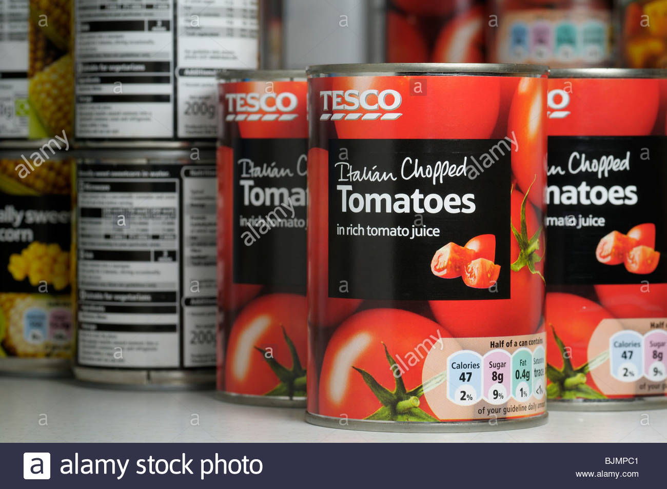 Close up of tins of Tesco Italian Chopped Tomatoes in a store cupboard, England UK - Stock Image