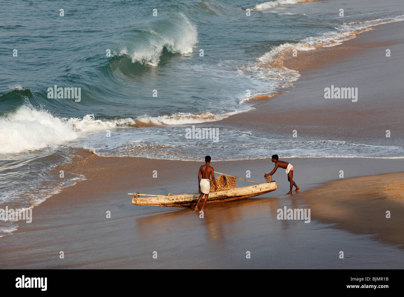 Two locals with a simple fishing boat on a beach south of Kovalam, Malabar Coast, Malabar, Kerala, southern India, - Stock Image