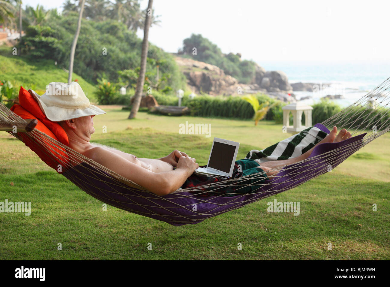 Man wearing a hat, lying in a hammock and relaxing while working with a netbook, Bethsaida Hermitage near Kovalam, - Stock Image