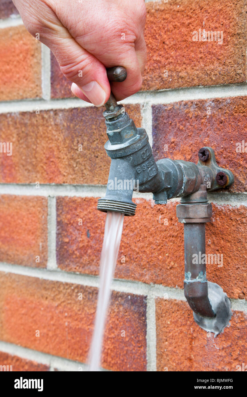 Person Turning On Water On An Outside Tap Fixed To