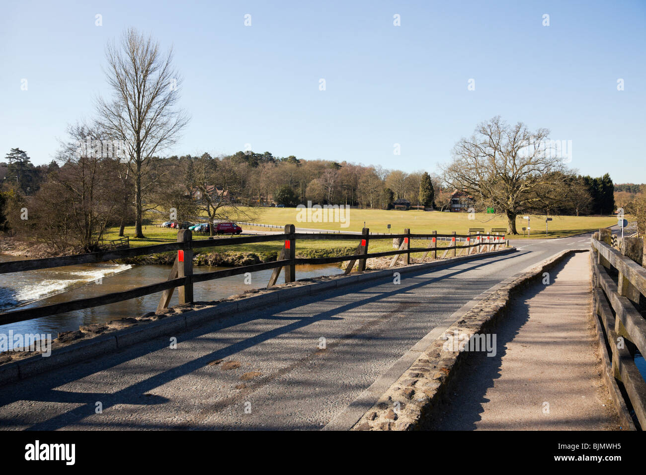Tilford, Surrey, England, UK, Europe. View to village green along the narrow road bridge crossing the River Wey. - Stock Image