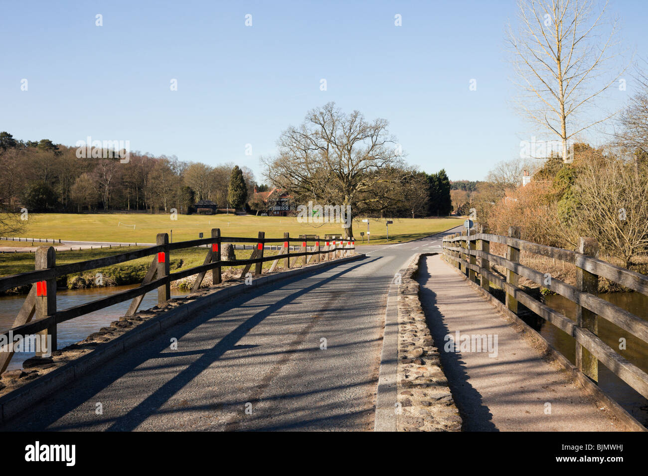 Tilford, Surrey, England, UK, Europe. View to village green along the ancient narrow bridge crossing the River Wey. - Stock Image