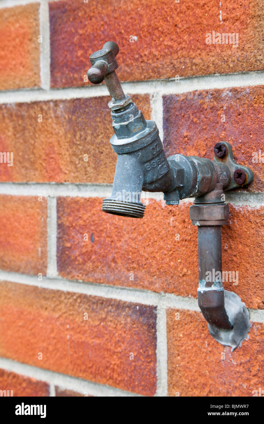 Outside tap switched off and fixed to a brick wall - Stock Image