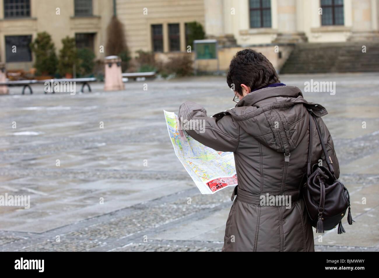 Woman tourist looking at a map outside Franzosischer Dom Gendarmenmarkt sculpture church Berlin Germany Europe - Stock Image