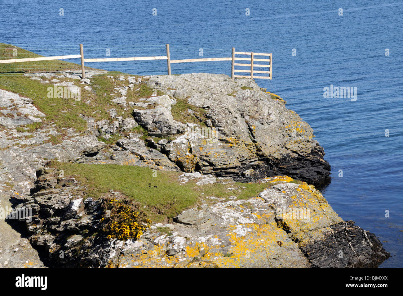 A fence goes right to the edge of a cliff above the sea. - Stock Image