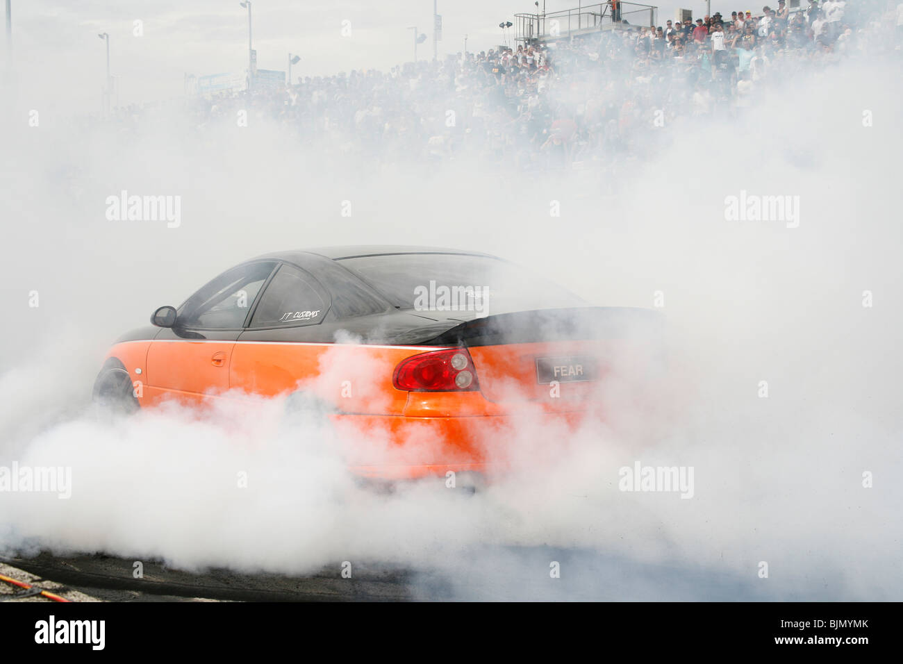 Australian burnout specialist, Fred Watson, performs a massive tire smoking burnout in his supercharged Holden Monaro - Stock Image