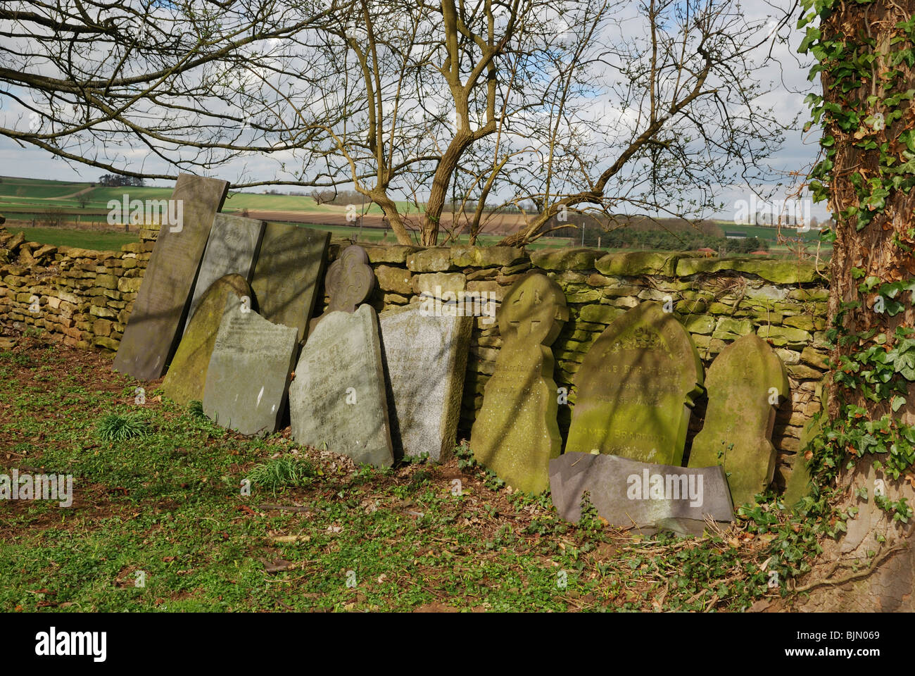 Discarded gravestones at St Wilfrid's church, Honington, Lincolnshire, England. - Stock Image