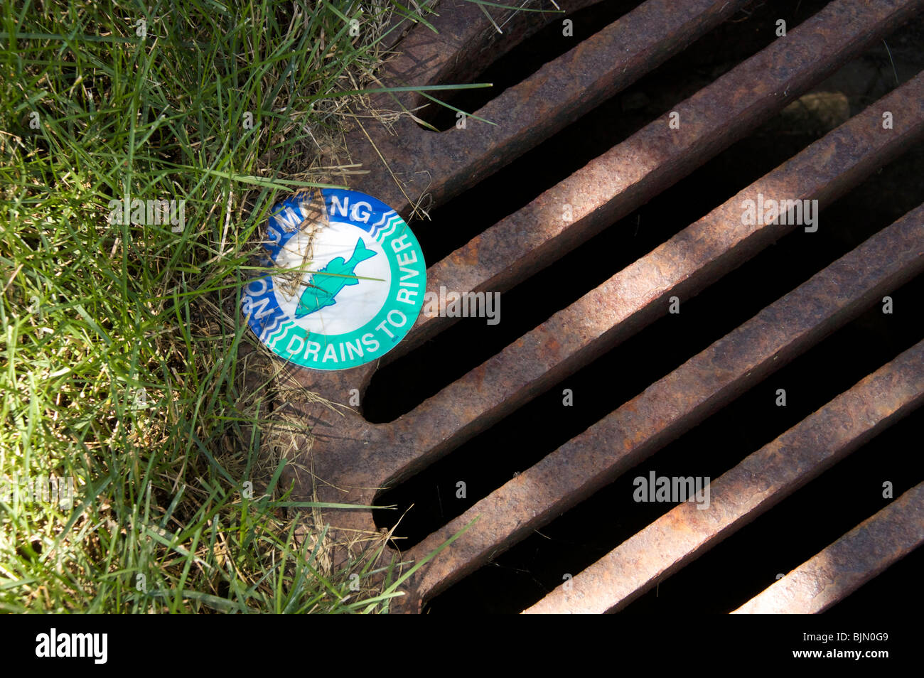 No dumping warning on storm drain to river. - Stock Image