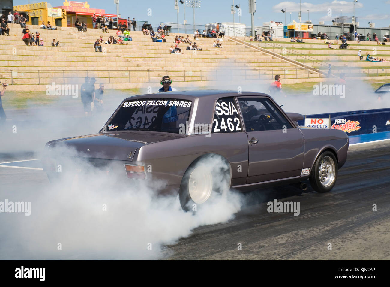 1960s Ford Cortina drag racing car performing a burnout prior to racing at the Perth Motorplex in Western Australia Stock Photo
