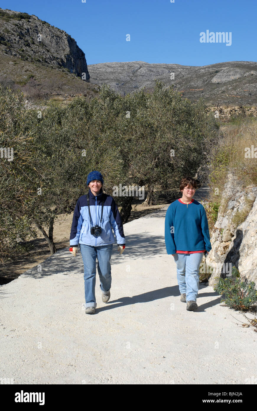 hikers walking on mountain track near Tarbena, Alicante Province, Comunidad Valenciana, Spain - Stock Image