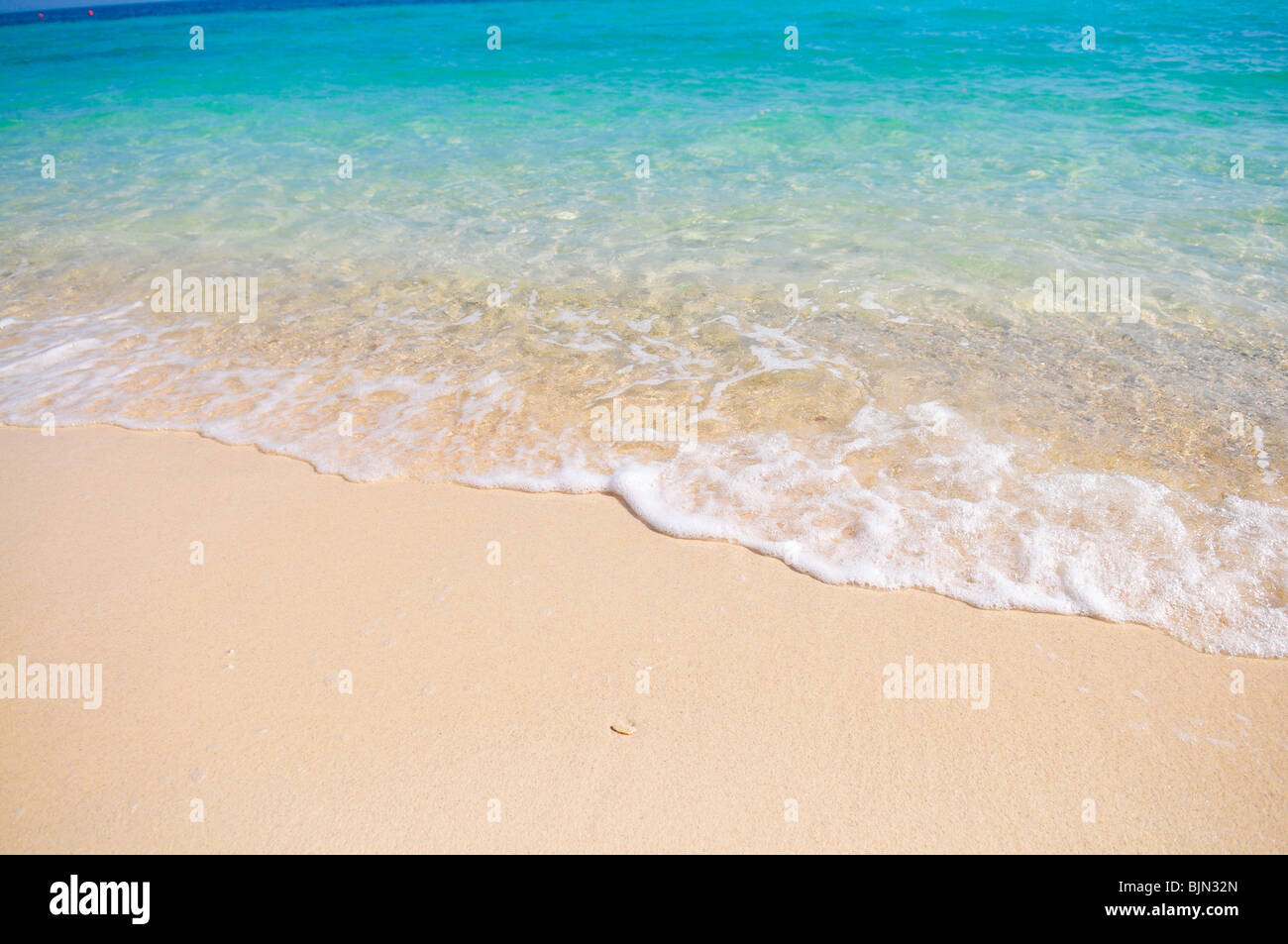 Tropical beach with white coral sand and calm wave - Stock Image