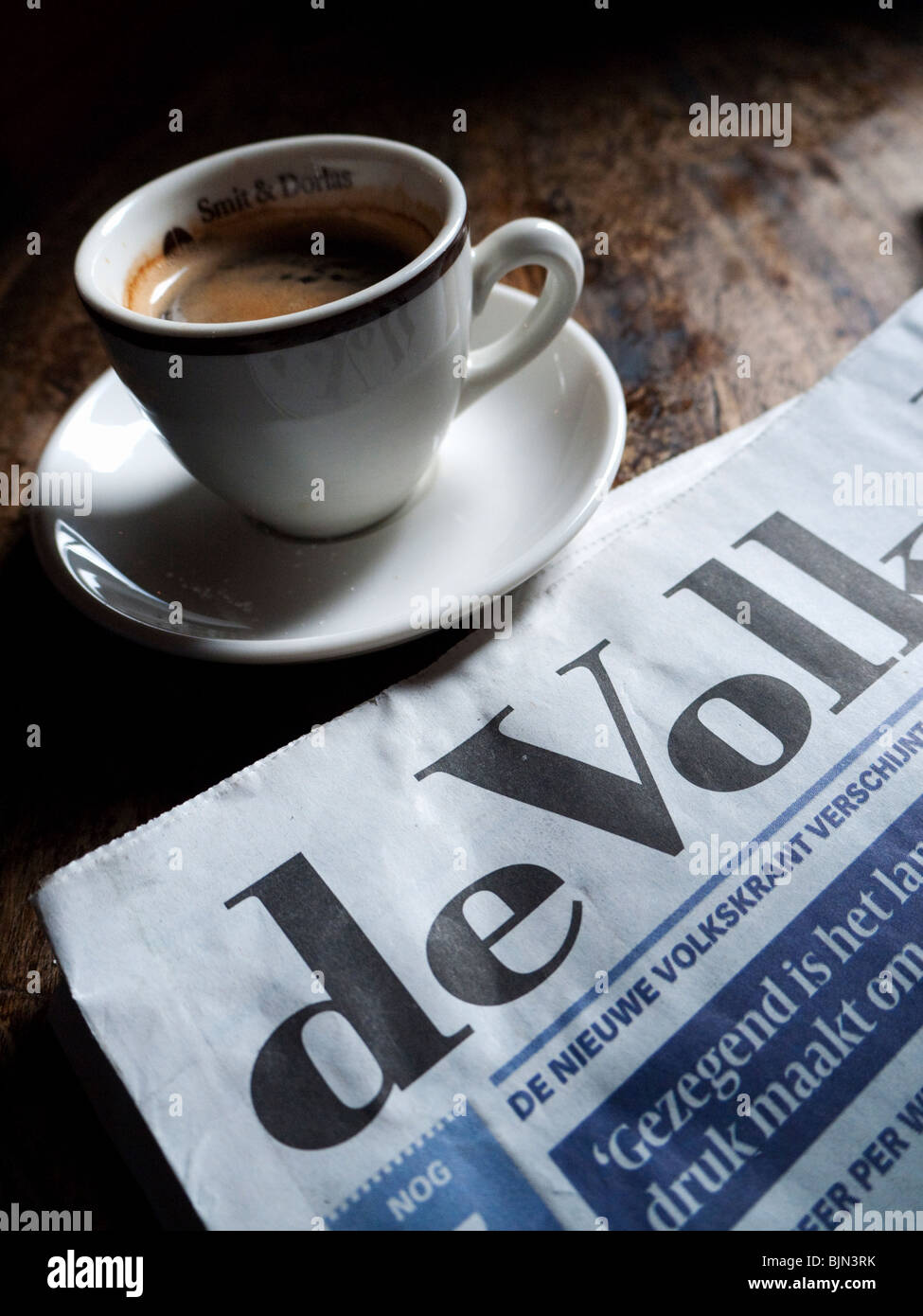Detail of Dutch newspaper and coffee cup in typical brown cafe in Utrecht in The Netherlands - Stock Image
