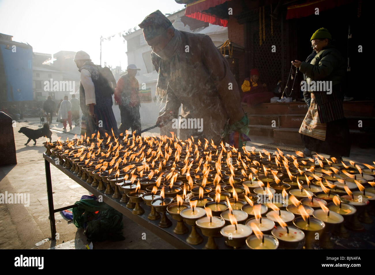 A man lighting candles outside the entrance to Boudhanath stupa in Kathmandu, Nepal - Stock Image