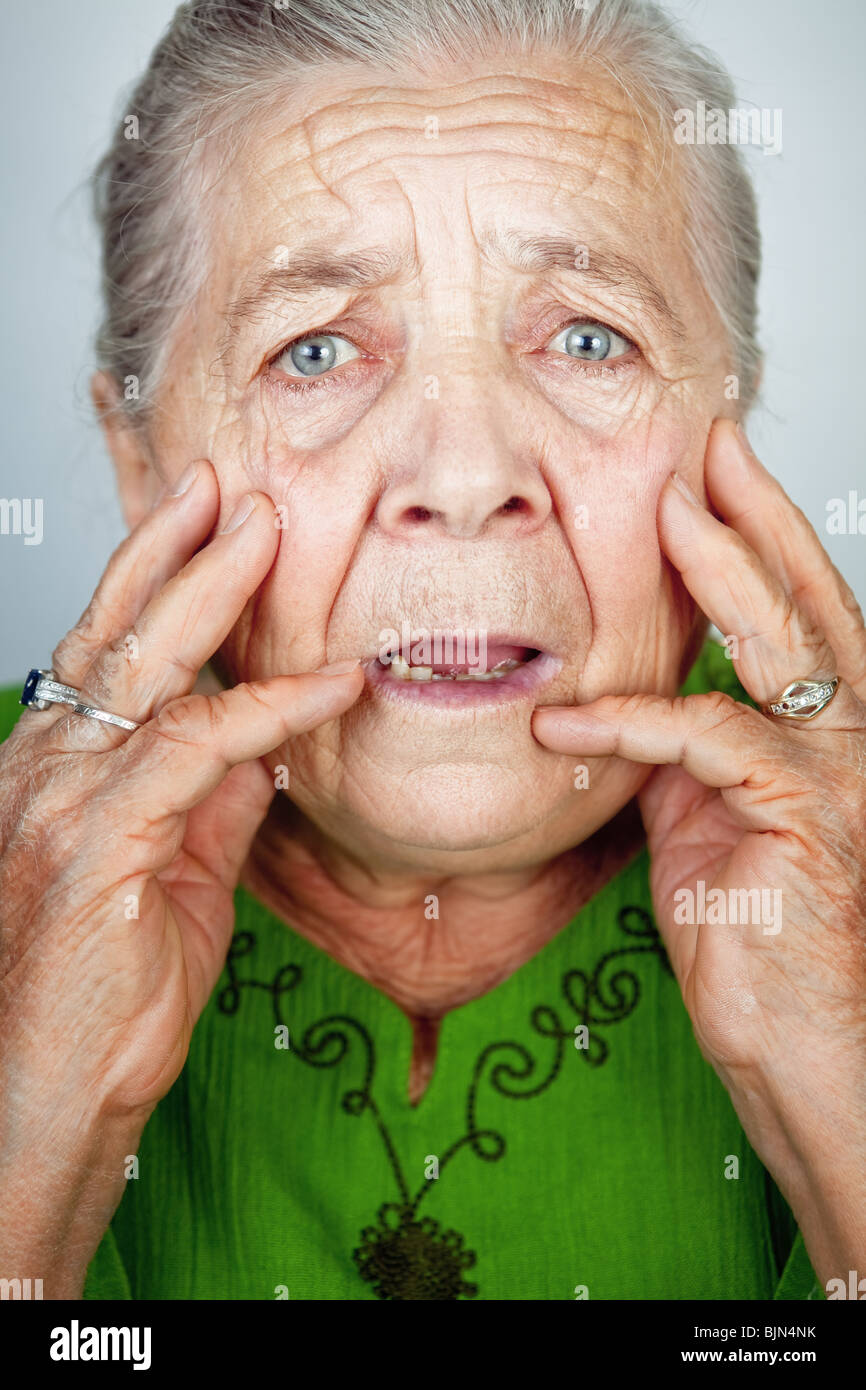 Portrait of scared and worried senior wrinkled lady - Stock Image
