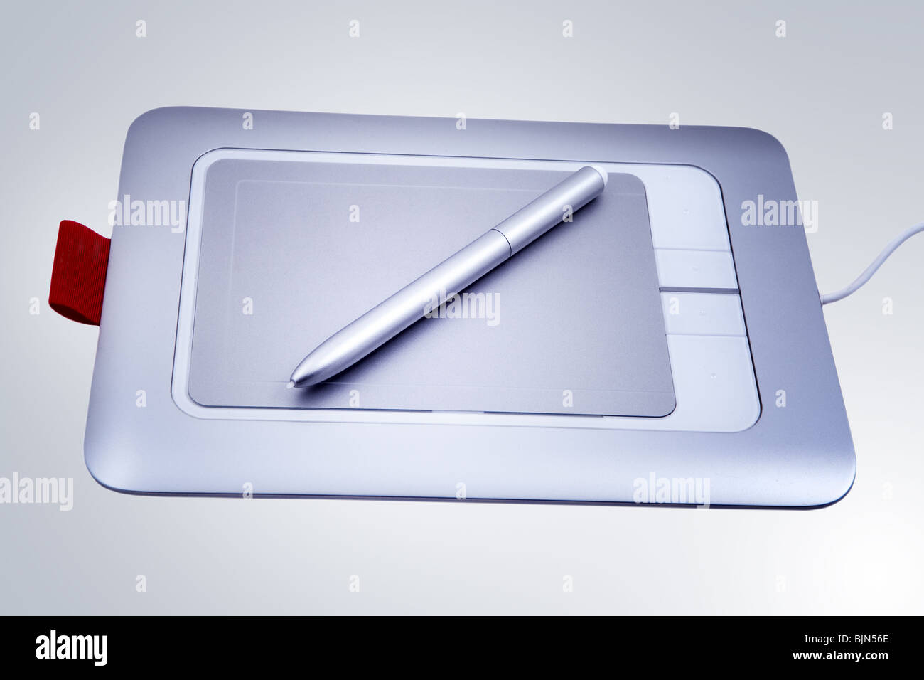 Electronic drawing pen tablet isolated on blue background - Stock Image