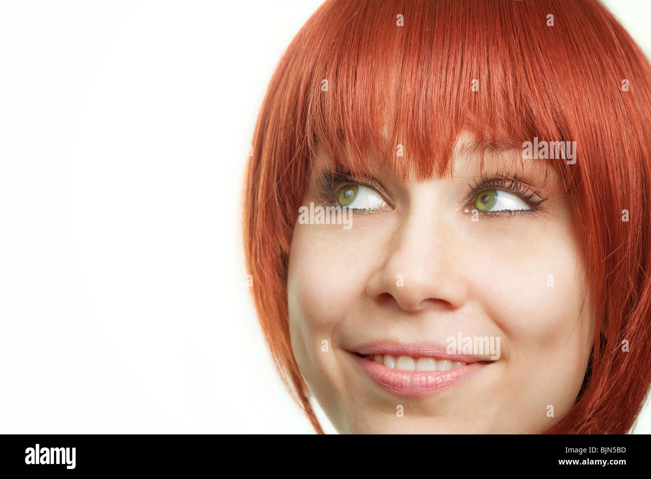 Face of young redhead woman having an idea - Stock Image