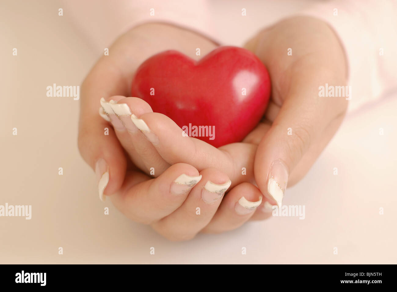 Young woman with beautiful long nails holding a wooden red heart ...