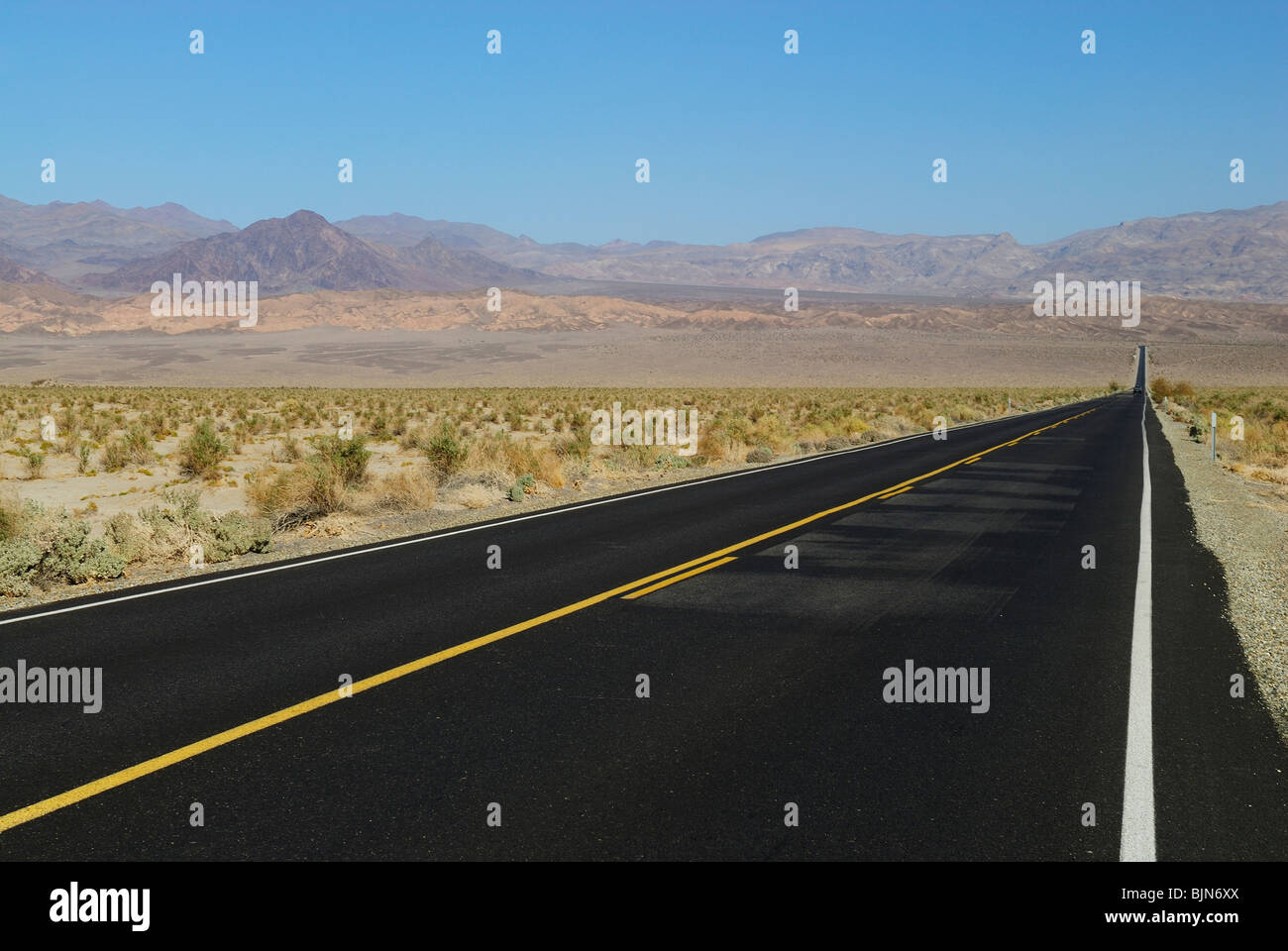 Long paved road crossing Death Valley, California state - Stock Image
