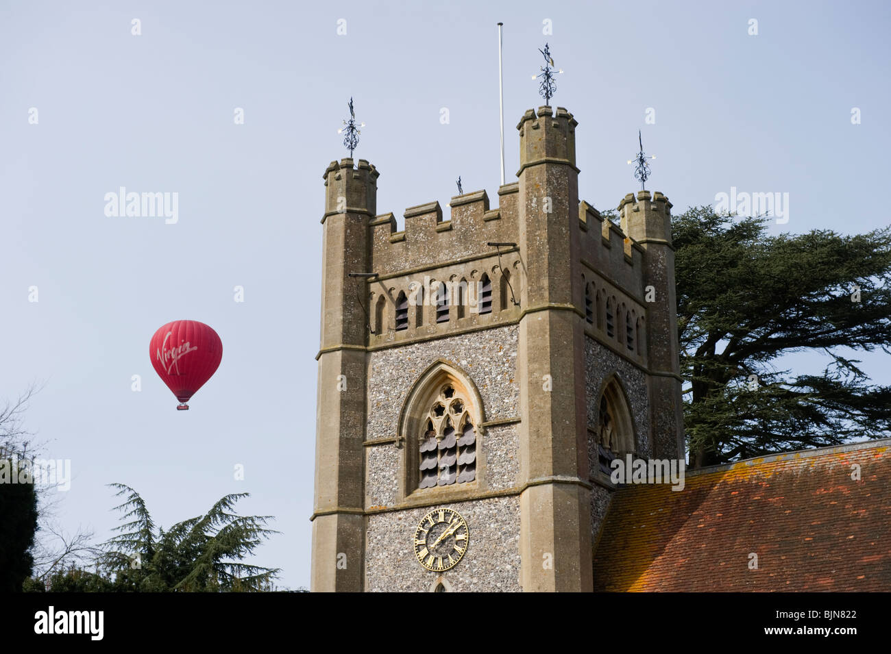 Virgin hot air balloon passing near to the church tower of St Mary the Virgin parish church of Hambleden Buckinghamshire - Stock Image