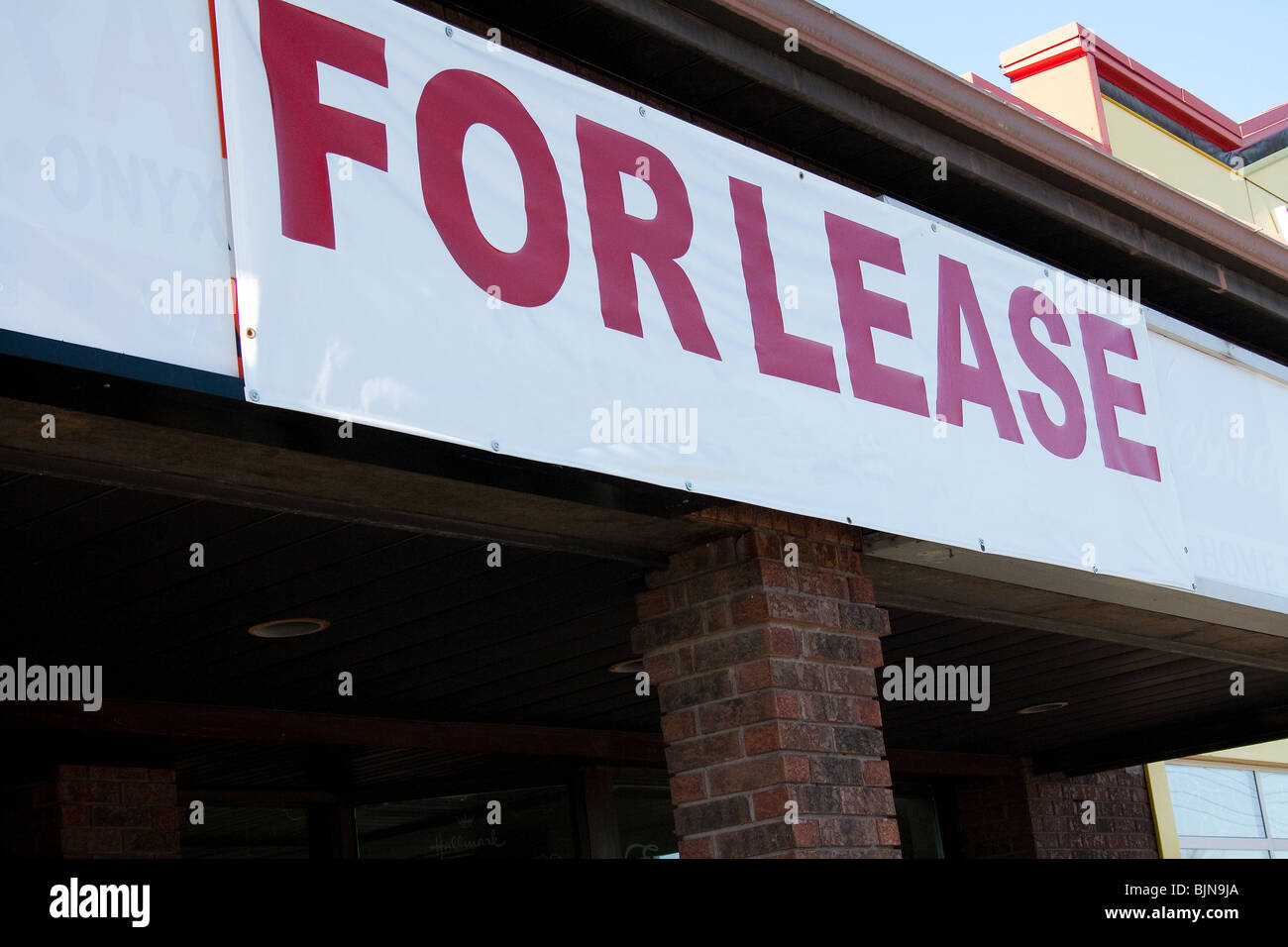 for lease rent sign empty plaza commercial space car front entrance parking lot strip mall real estate rental market - Stock Image