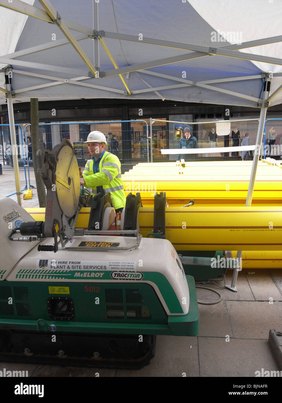 A plant operator with a machine for jointing plastic pipe for lining an existing gas main in Middlesbrough town - Stock Image