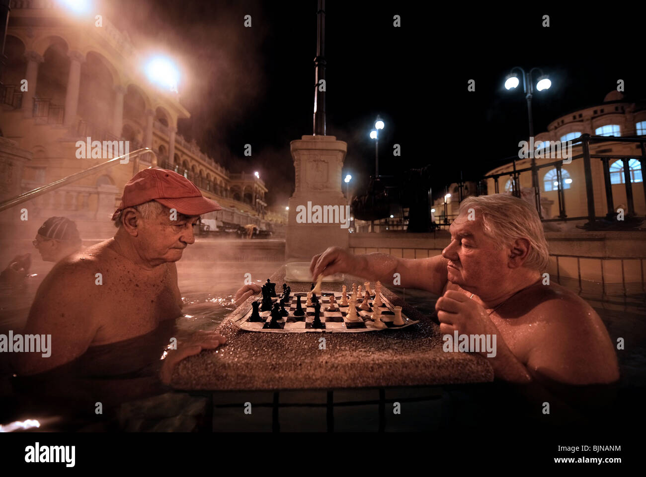 Men playing chess in the Szechenyi Baths on a cold winter night in Budapest, Hungary - Stock Image