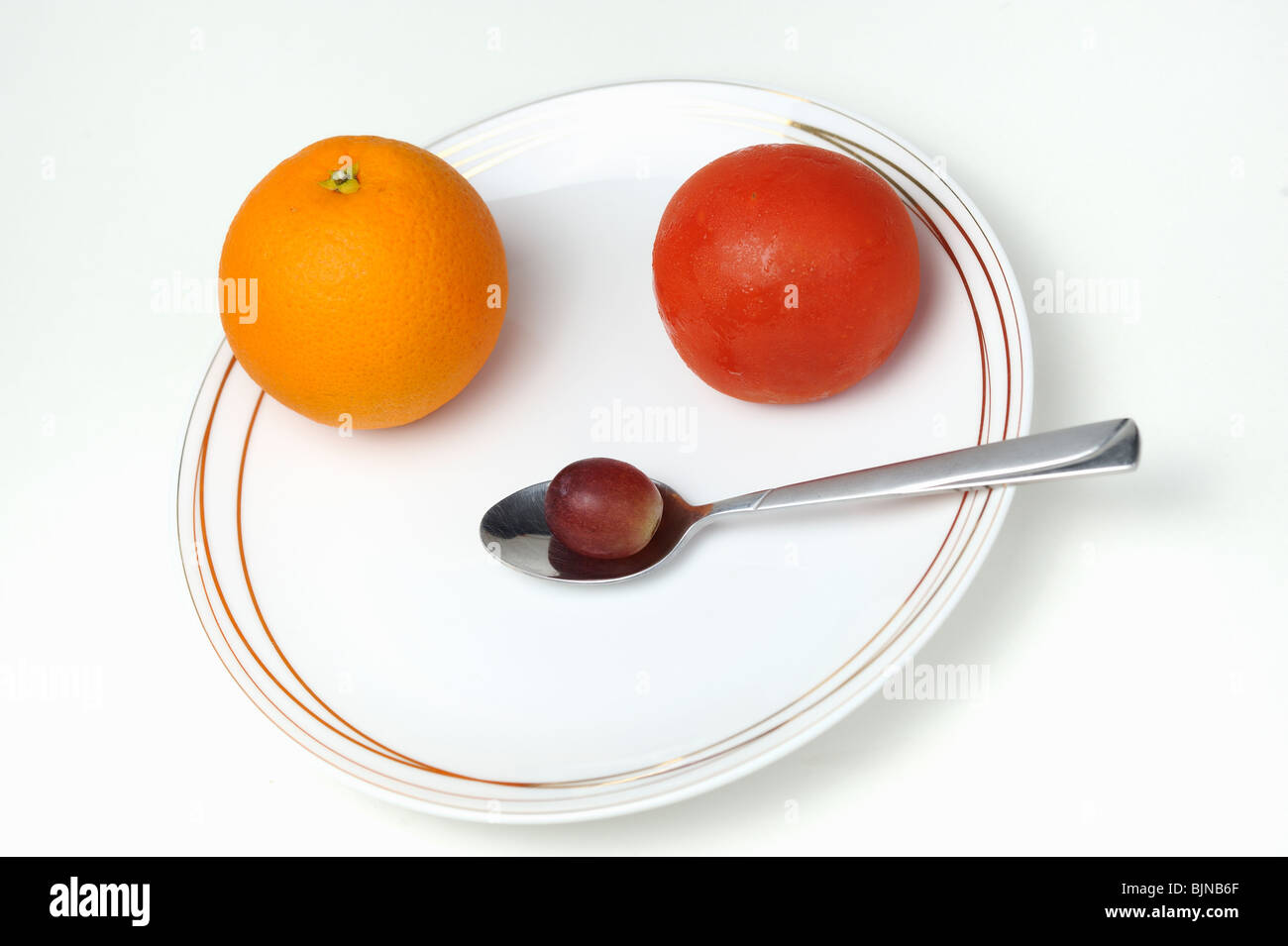 Plate and spoon with one Orange, one tomatoe, one grape, on white background - Stock Image