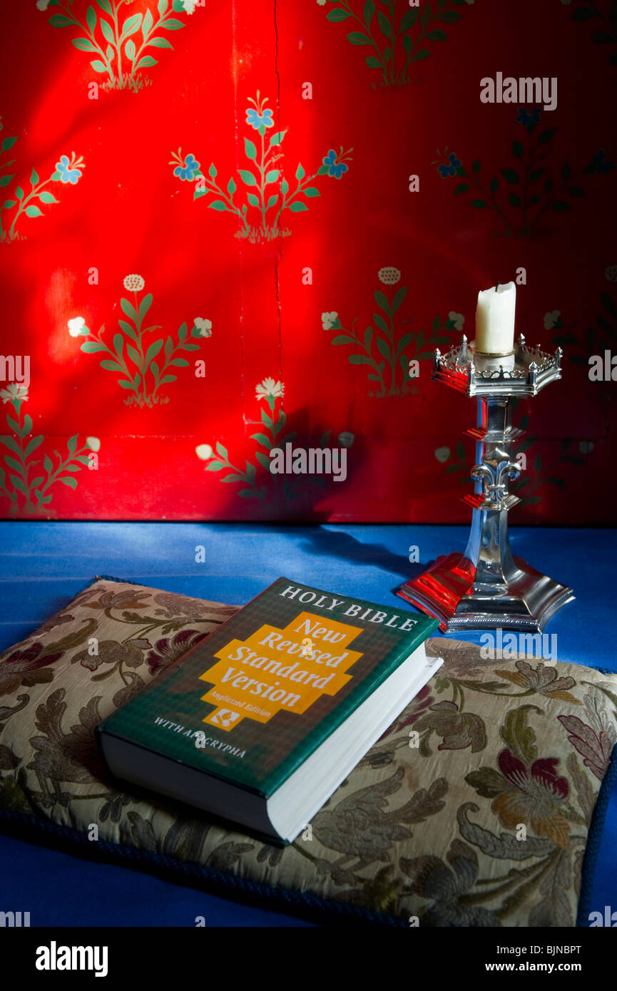 A copy of the Holy Bible on a cushion with a candlestick on Hambleden parish church altar Buckinghamshire UK - Stock Image