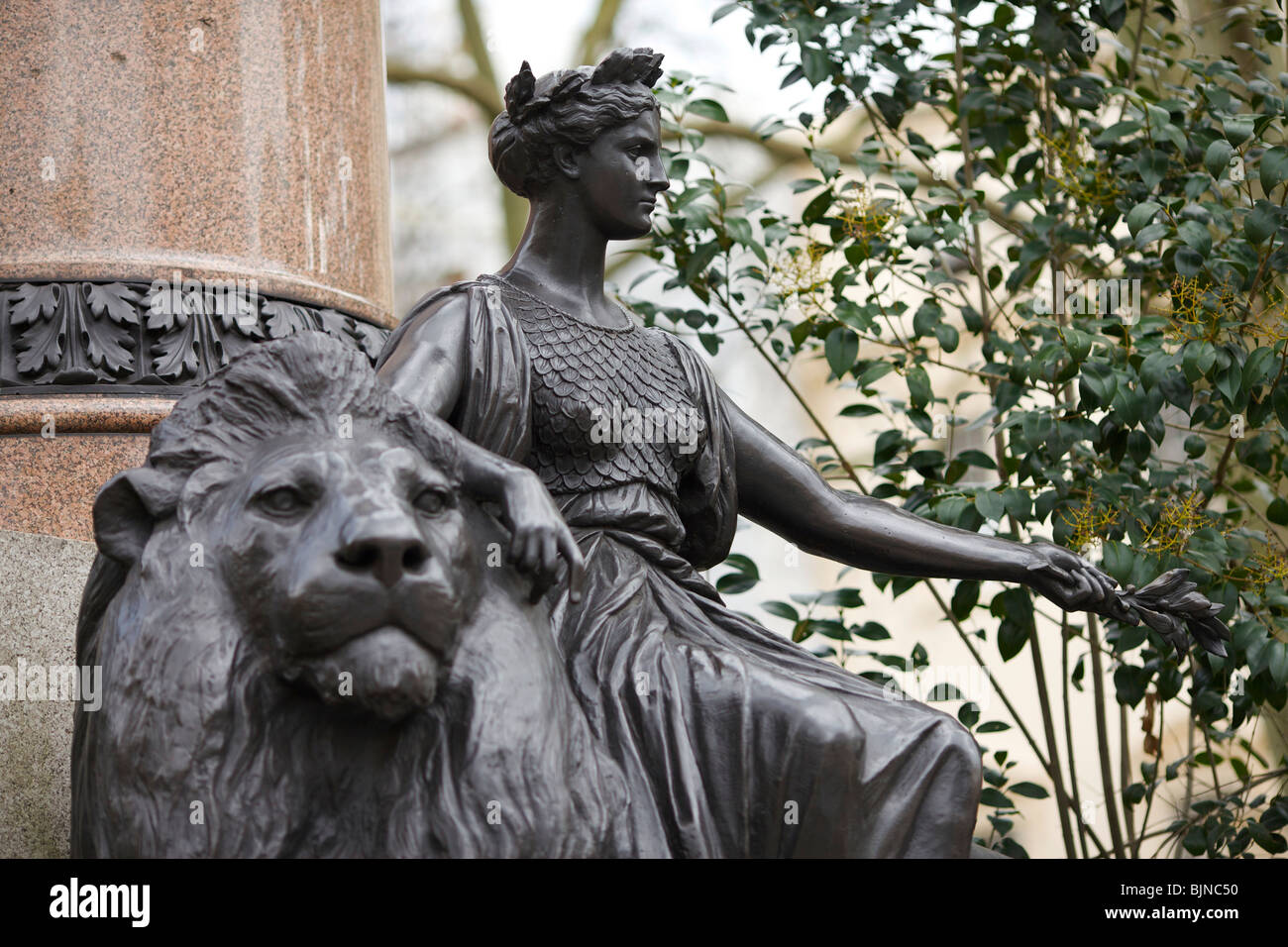 Allegorical statue of Britannia and Lion at the base of Sir Colin Campbell column in waterloo place in London - Stock Image