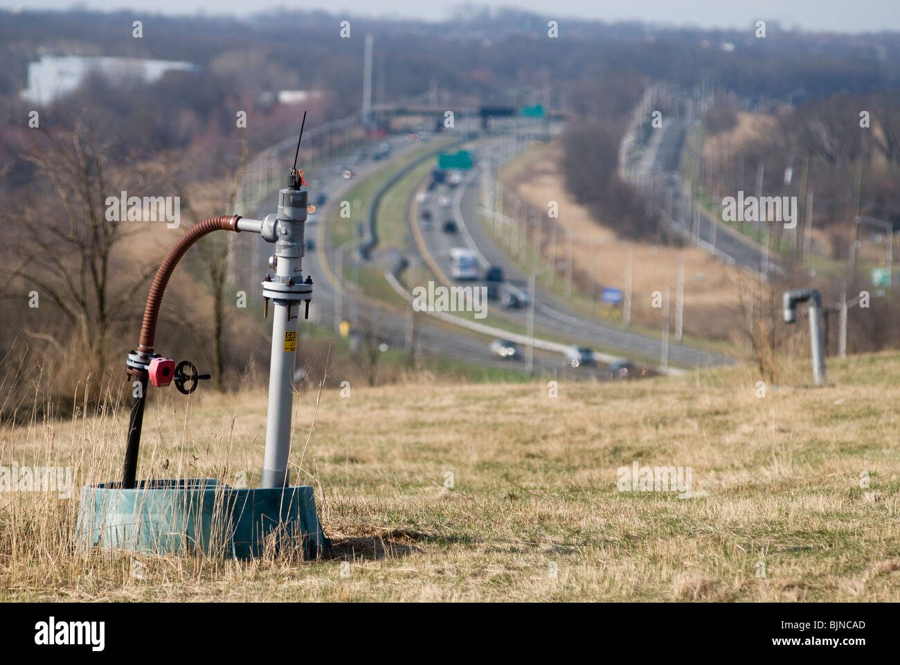An active methane well head on the Fresh Kills Landfill is seen with traffic on the West Shore Expressway - Stock Image