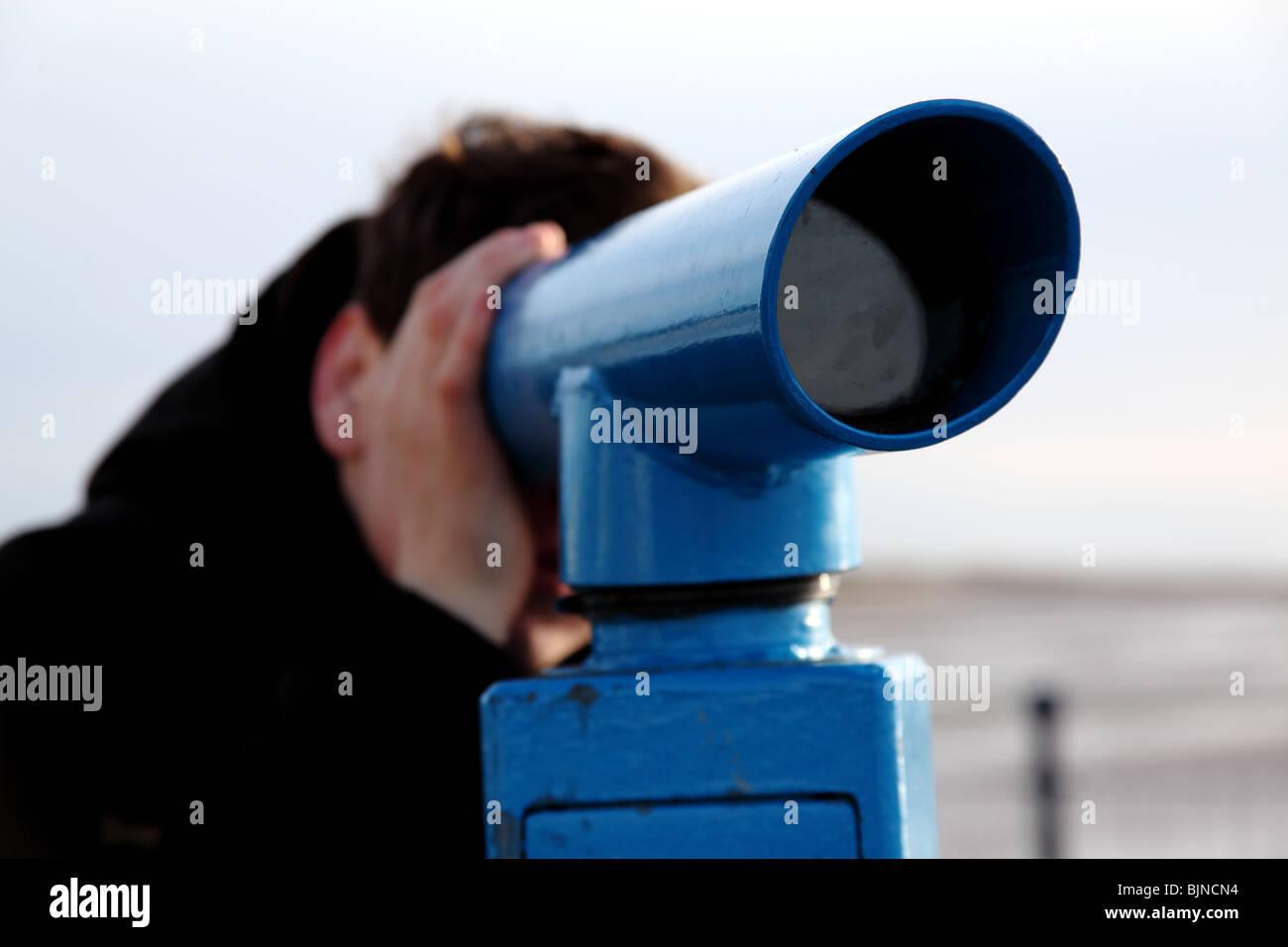 man looking through a telescope - Stock Image