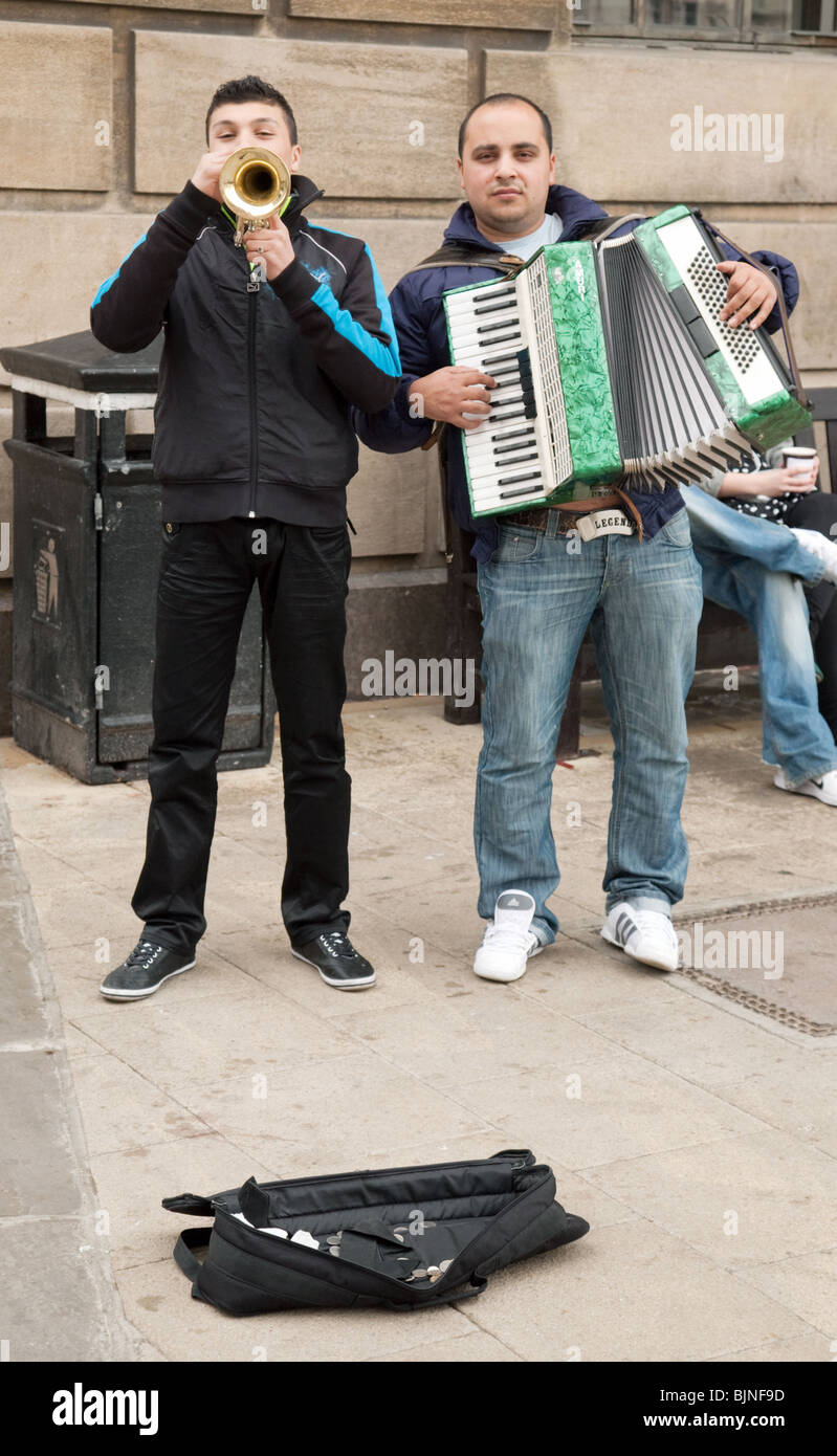 Two buskers playing horn and accordion in the market square, Cambridge, UK - Stock Image