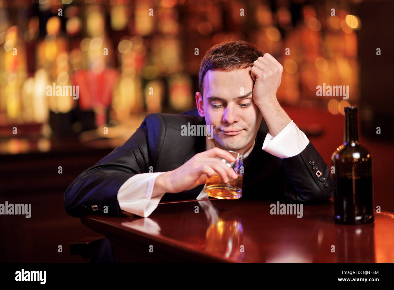 Young drunk man drinking whiskey in the bar Stock Photo