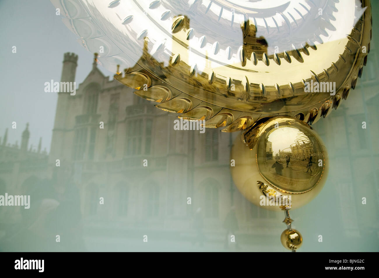 The pendulum of the Grasshopper Clock, Corpus Christi College cambridge, with Kings College reflected in the window, Stock Photo