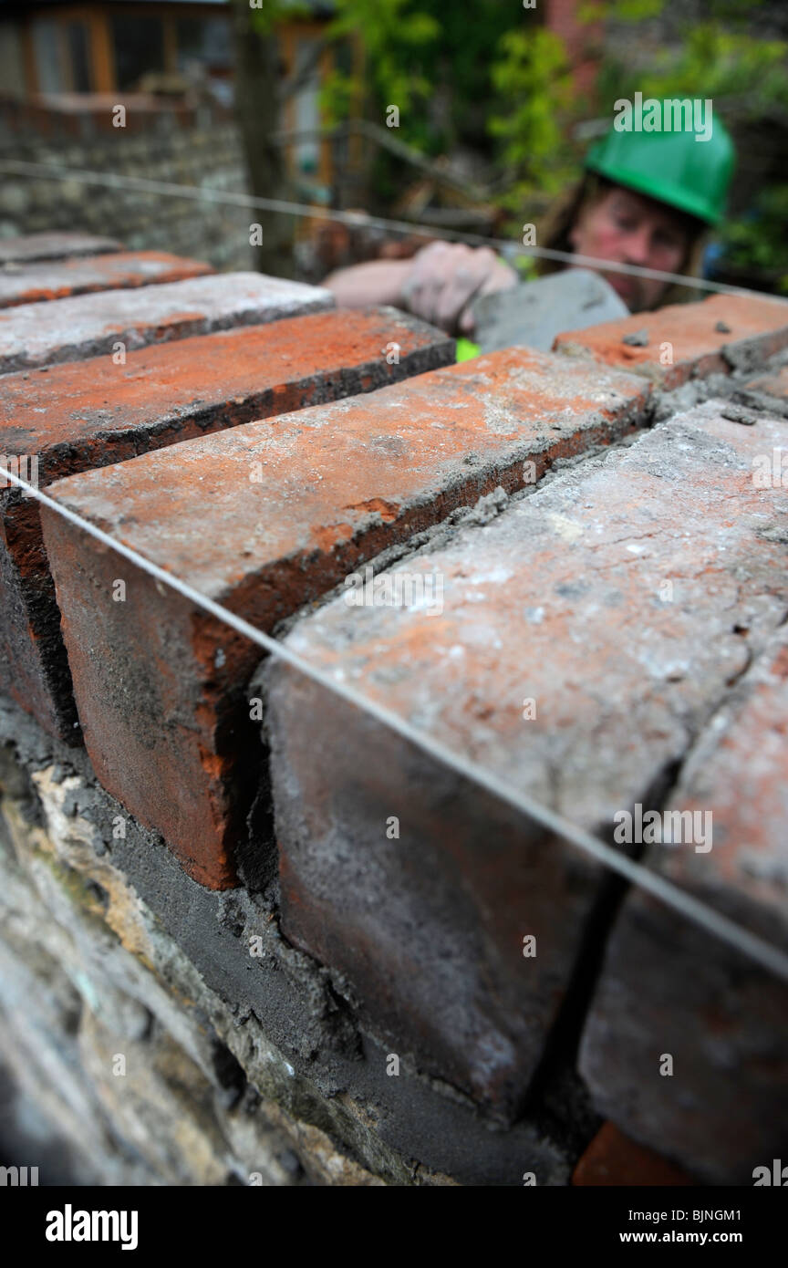 Building of a garden wall with Cotswold stone and reclaimed red bricks UK - Stock Image