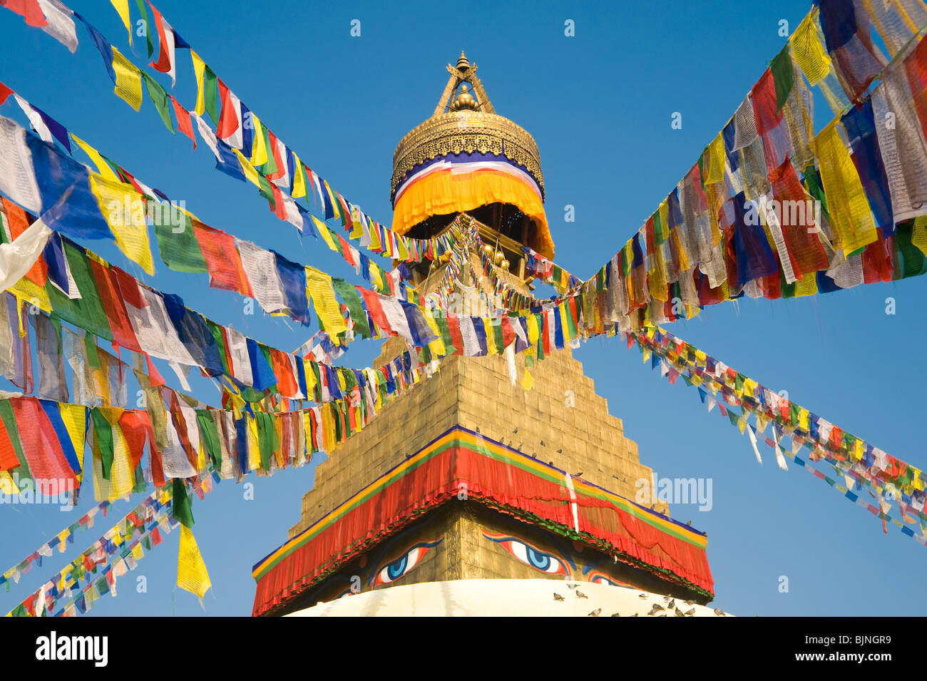 The top of Boudhanath stupa with many Tibetan prayer flags in Kathmandu, Nepal Stock Photo