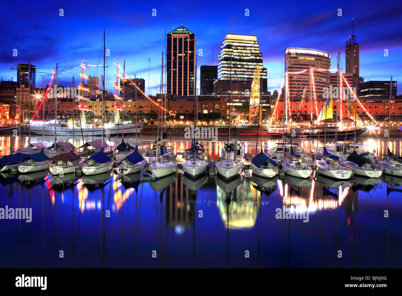Close Front view of Puerto Madero yacht  club view at dusk with water reflections and lights, Buenos Aires, Argentina - Stock Image