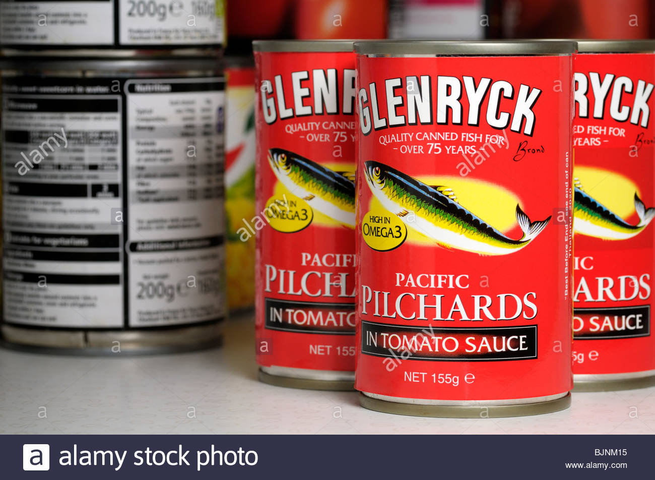 Close up of tins of Glenryck Pilchards in a store cupboard, England UK - Stock Image