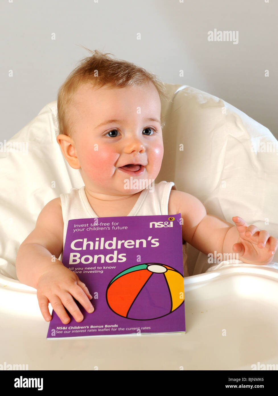 Baby boy with National Savings Childrens Bonds leaflet - Stock Image