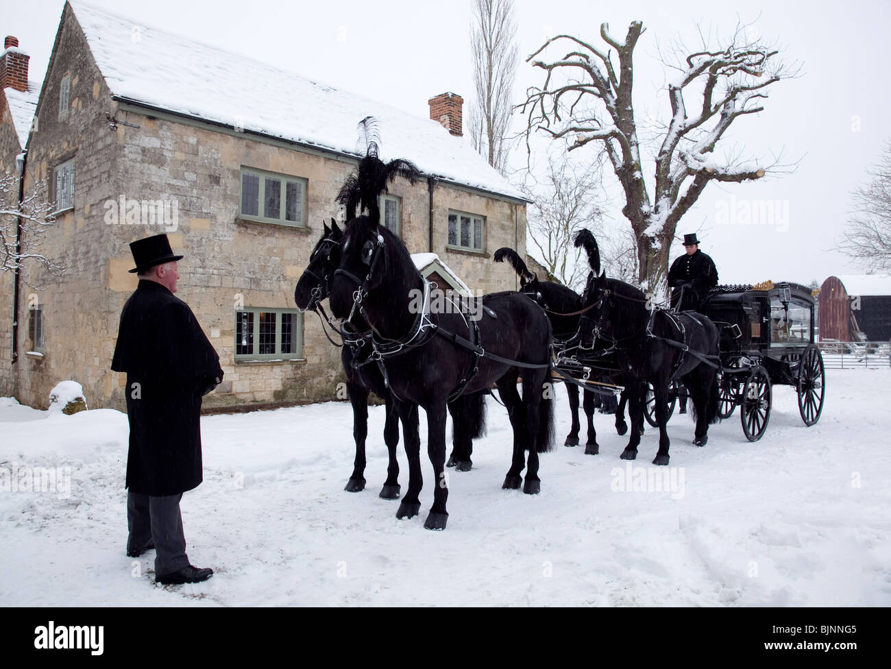 Traditional old fashioned Horse drawn funeral carriage in snow with four horses ready to leave for church service - Stock Image